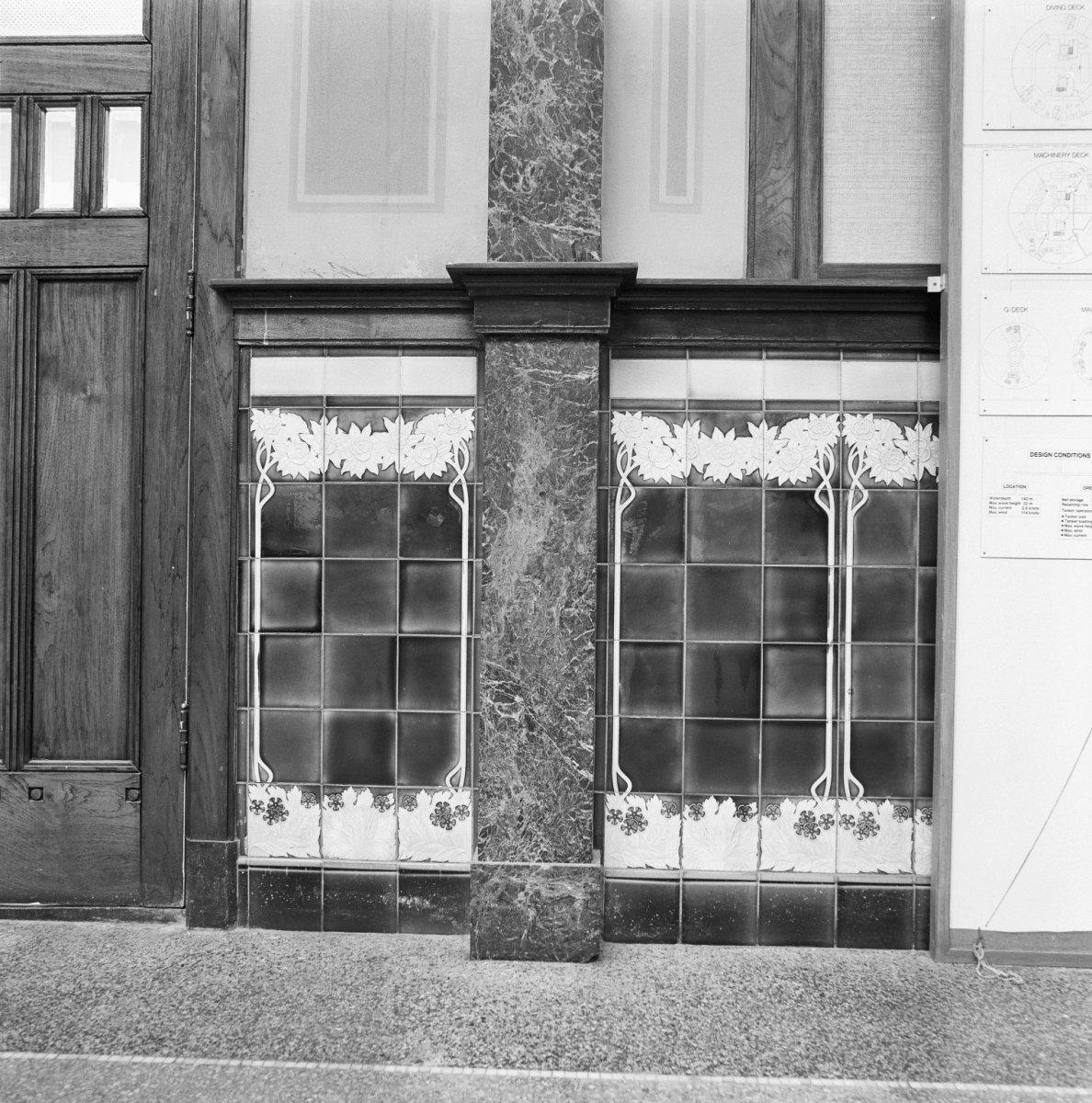 Ontvangsthal, detail van de zijwanden, die bestond uit tegels met eikenhouten afzettingen.